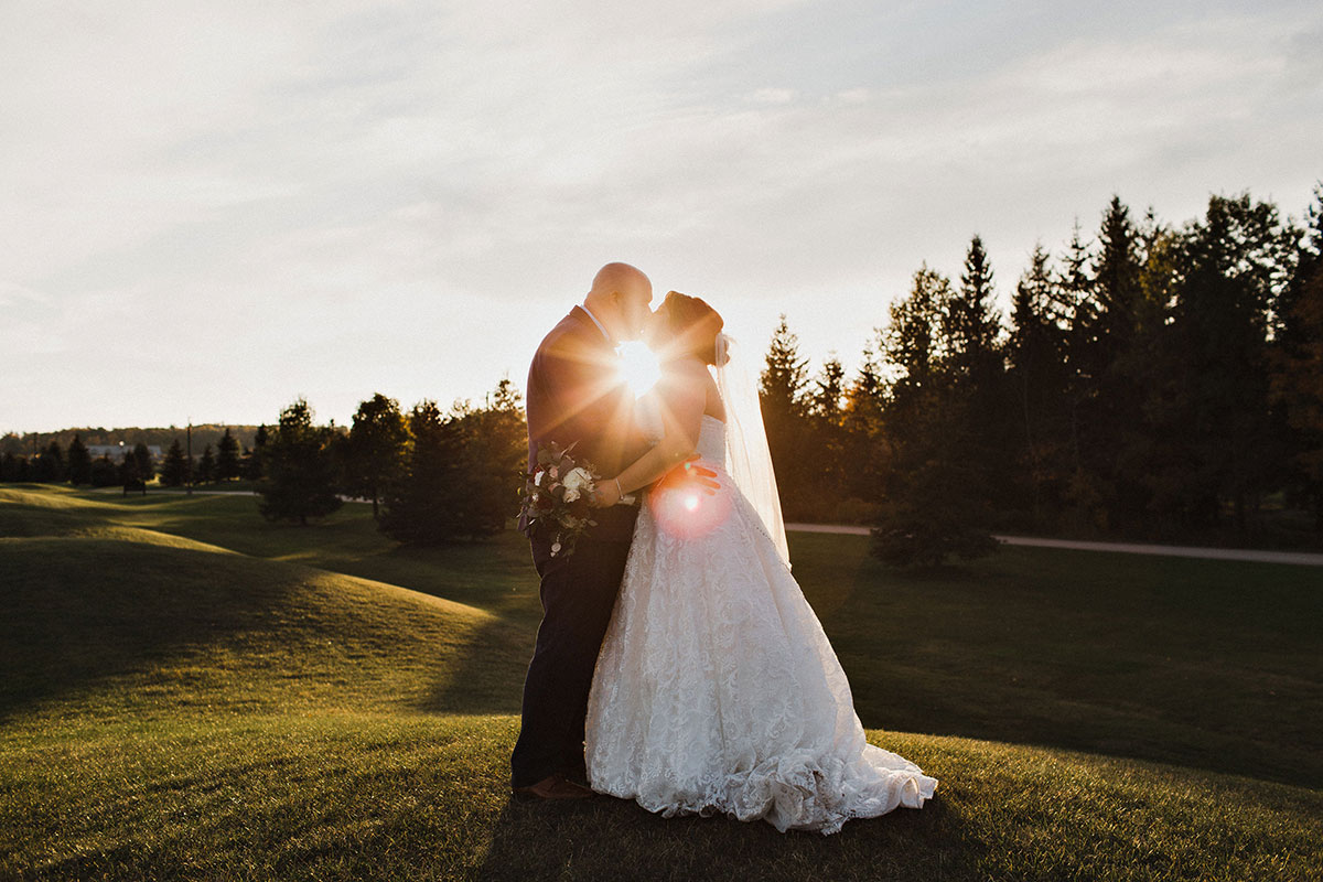 Wedding couple kiss in the sunset at Crosswinds in Burlington